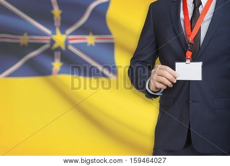 Businessman Holding Name Card Badge On A Lanyard With A National Flag On Background - Niue