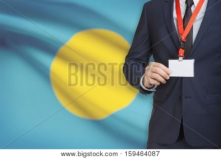 Businessman Holding Name Card Badge On A Lanyard With A National Flag On Background - Palau