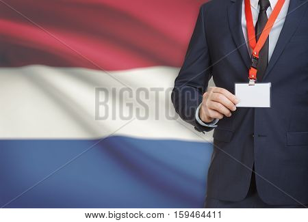 Businessman Holding Name Card Badge On A Lanyard With A National Flag On Background - Netherlands