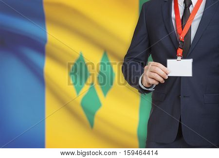 Businessman Holding Name Card Badge On A Lanyard With A National Flag On Background - Saint Vincent
