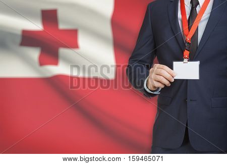 Businessman Holding Name Card Badge On A Lanyard With A National Flag On Background - Tonga