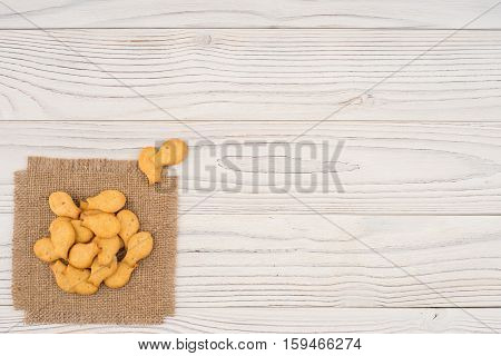 Cracker goldfish on sackcloth and wooden table. Top view.