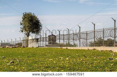 Fence with razor wire on top of fencing surrounds industrial area
