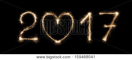 2017 New year from sparkler firework on black background with heart shape, love symbol and greeting. Two thousand seventeen numbers. Illuminated date figures for calendar