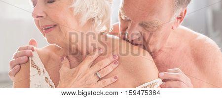 Older Man Kissing Wife In Lingerie