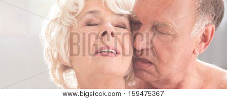 Close-up of older people faces in ecstasy while touching and kissing poster