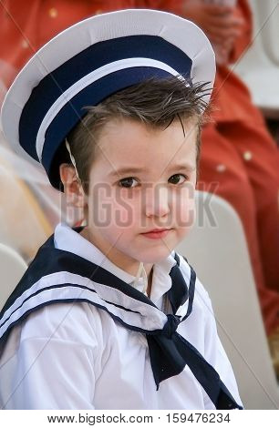 Little sailorBoy with snot in his nose dressed in navy costume