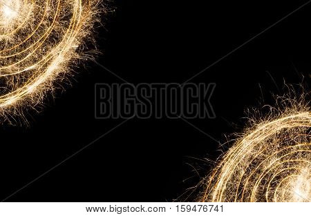 New year party burning sparkler circles frame on black background. Glowing holiday sparkling hand fireworks border with copy space, shining fire. Christmas light.