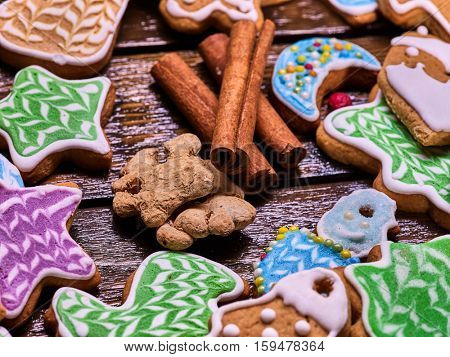 Christmas gingerbread cookies cinnamon sticks on woden table and ginger root.