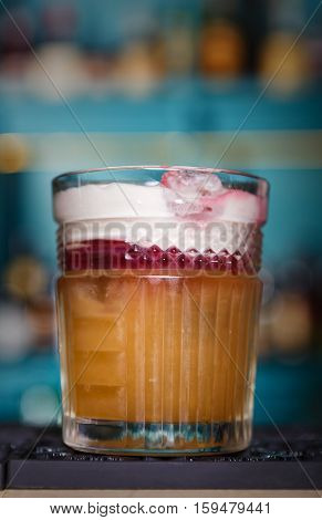 Closeup of creamy sweet exotic party alcohol cocktail in restaurant at bar background. Glass on bar table, refreshing drink with straw. Cream soda, vertical image