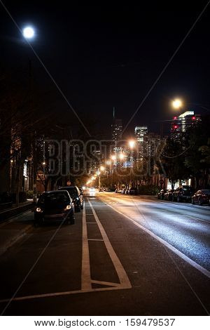 Dark City Street at Night with Moon