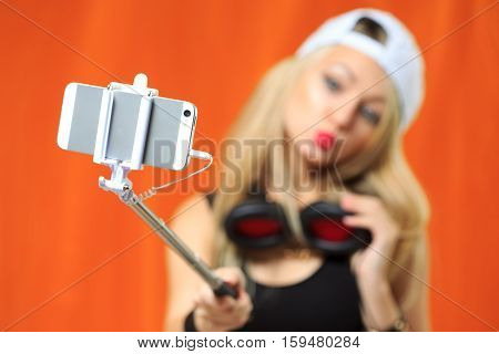 cute beautiful girl in a hipster hat making selfe photo on the phone with selfe stick