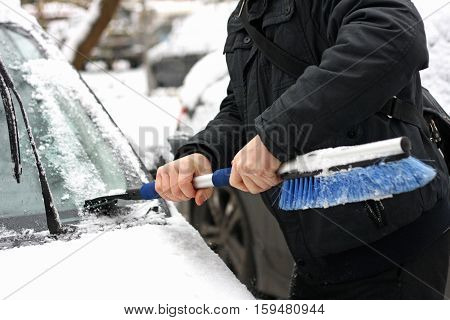 Winter. Snow-covered car. A man cleans the car from snow with the help of special brushes.