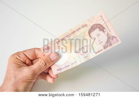 Man Holding Fifty Bhutanese Ngultrum Banknote In His Hand