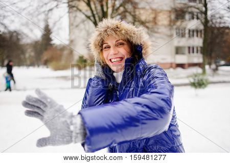 The woman turns aside from the snowballs flying to her. Someone fires at her snowballs. She has exposed hand forward and cheerfully laughs. All ground is completely covered with fluffy snow.