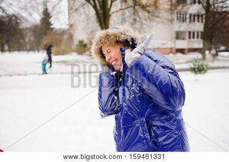 Woman turns aside from the snowballs flying to her. Someone fires at her snowballs. She pulls a hood over the face and cheerfully laughs. All ground is completely covered with fluffy snow.