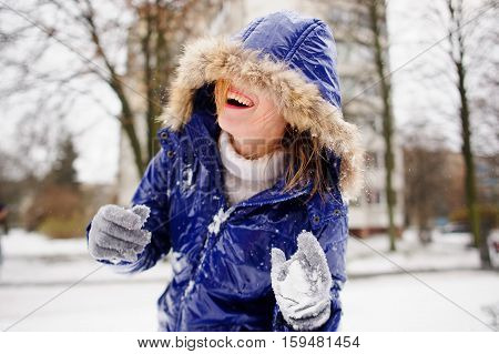 Laughing young woman after fight by snowballs. The woman's face is half hidden by a hood. A coat and gloves in snow wet hair. Woman was tired of a game and laughs from pleasure.