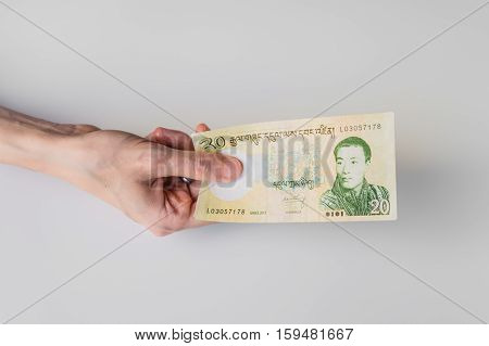 Woman Holding Twenty Bhutanese Ngultrum Banknote In Her Hand