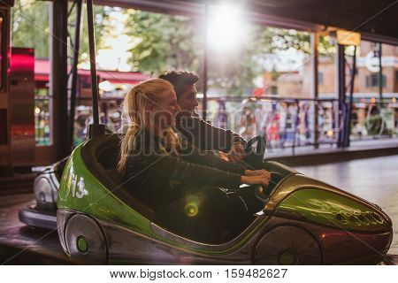 Happy young couple driving a bumper car at amusement park. Young man and woman riding bumper car at fairground.