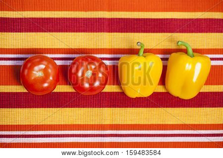 Healthy vegetables on the table covered with a tablecloth with stripes in the garden. Yellow peppers and red tomatoes rich in vitamins are a very good choice for a healthy diet. Natural light and good mood.