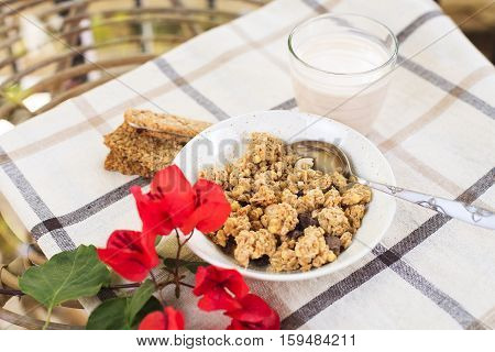 Healthy morning breakfast on the table with tablecloth and red flowers in the garden. Granola, sweet cookies and drinking yogurt in the glass. Natural light. Good morning mood.