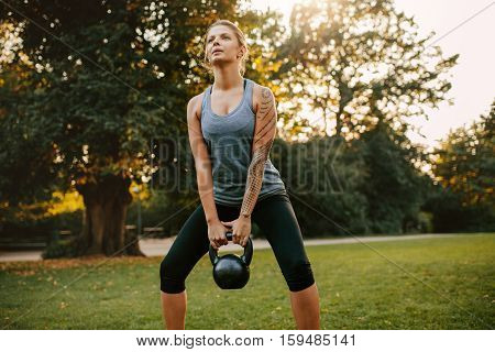 Portrait of strong young woman exercising with kettlebell weights in the park. Fit and muscular woman training at city park in morning.
