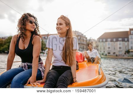 Shot of teenage women sitting on pedal boat with a man in background. Happy young friends enjoying boating in the lake.