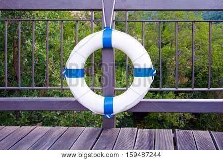White life buoy hanging from the balcony with purple painted iron railings and wooden floor. Forest in the background