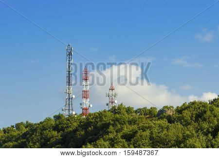 Three Telecommunication (GSM) towers with TV antennas satellite dishes and repeaters at the top of a hill on a blue sky and a cloud on background