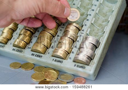 Hand holding one euro coin changing money in a very used and dirty coin holder