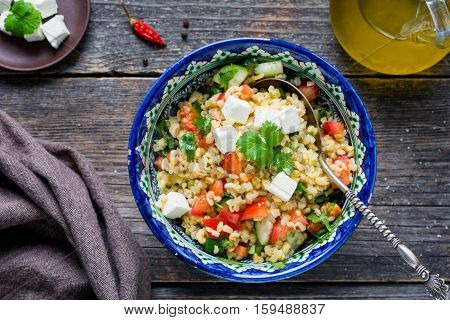 Tabbouleh salad with tomato, olive oil, parsley and white cheese served in ethnic middle eastern bowl on rustic table. Top view