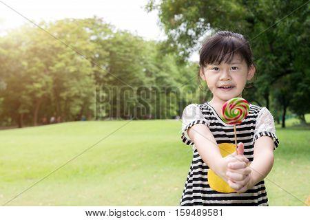 Asian little girl eating lollipop outdoors in spring park