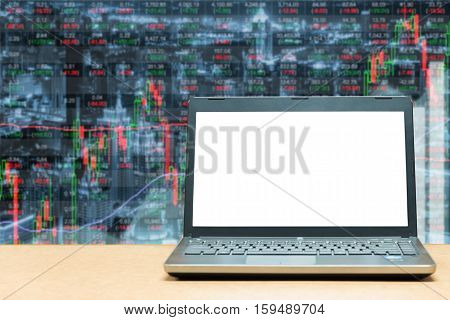 Laptop with blank screen on table with stock exchange market business trading graph. Business marketing trade concept.
