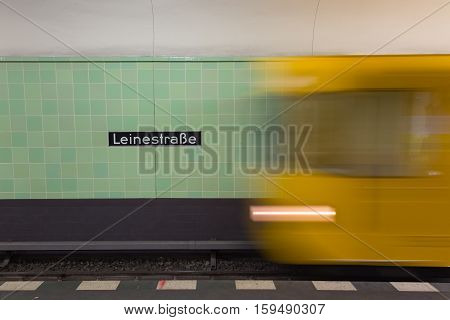 Yellow subway train in Motion. Berlin Leinestrasse sign visible on the wall of underground station.