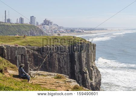 Fisherman Over The Cliffs And Waves At Torres Beach