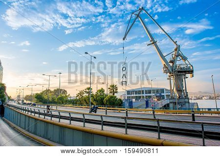 Part view of the port in Piraeus with an old crane and the peripheral road under a blue sky at sunset