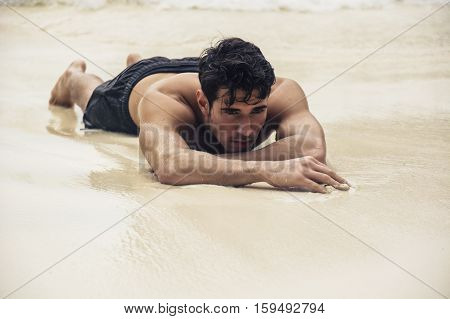 Half body shot of a handsome young man laying on a tropical beach in Phuket Island, Thailand, shirtless wearing boxer shorts, showing muscular fit body