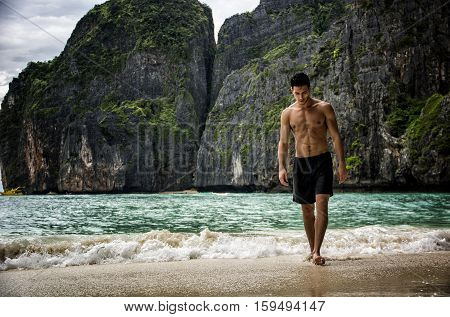 Full body shot of a handsome young man standing on a beach in Phuket Island, Thailand, shirtless wearing boxer shorts, showing muscular fit body