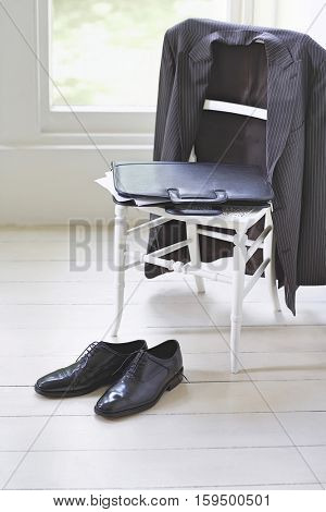 Business suit; case and formal shoes at home