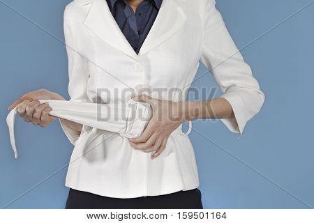 Midsection of a businesswoman adjusting belt against blue background