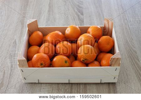 Bunch of fresh tangerines oranges  Fresh fruit tangerines in a wooden box  tangerines