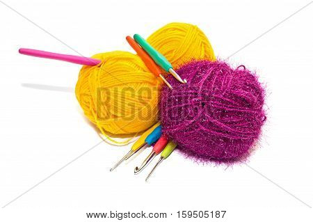 Hooks for knitting and balls of woolen skein are isolated on a white background