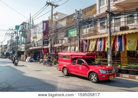 CHIANG MAI, THAILAND - FEBRUARY 3, 2016: Iconic traditional red truck taxis roaming the streets of Chiang Mai. Chiang Mai is a major tourist destination in northern Thailand.