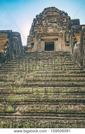 Stone old steps covered with moss leading to Angkor Wat stone tower, Siem Reap, Cambodia.