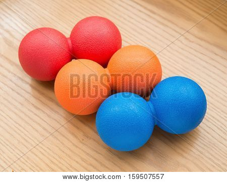 red and orange and blue small massage balls on a wood table