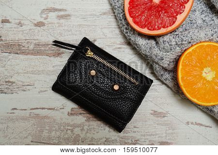 Fashion concept. Little black women's purse and citrus on a sweater a wooden background. View from above