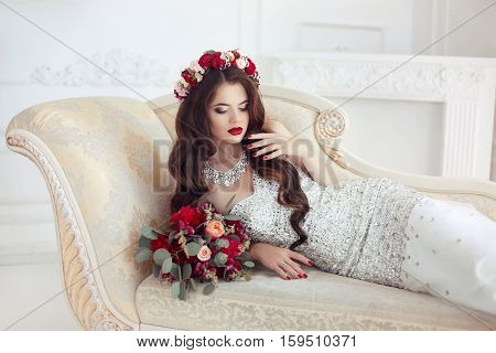 Beautiful Brunette Bride Lying On Classic Elegant Sofa, Baroque Style Ornaments. Makeup. Long Wavy H