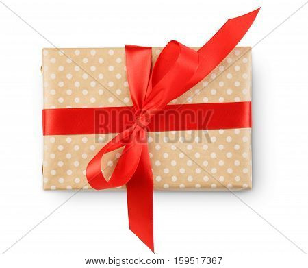 Gift box wrapped with dotted beige paper and red satin ribbon top view, isolated on white background. Modern present for any holiday, christmas, valentine or birthday