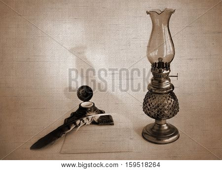 Blank paper card oil lamp and inkwell with a quill pen. Photos with the effect of natural canvas in sepia tone.