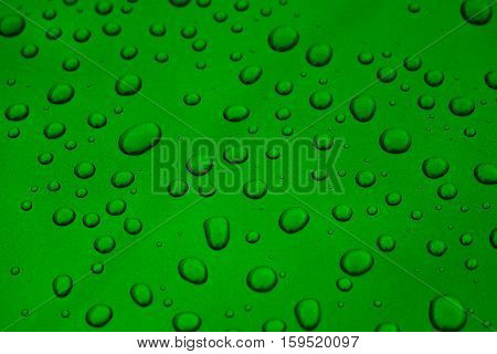 rain drops on green car paint threated with hydrophobic coating, shallow focus